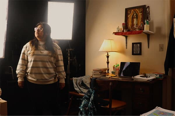 Young woman in glasses and a striped shirt standing in an office