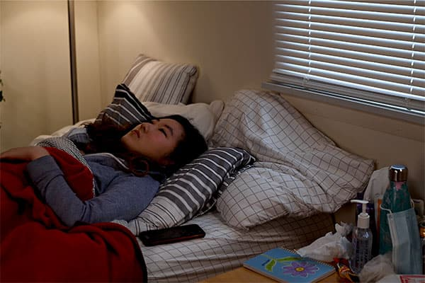 Young woman stares at ceiling while lying in bed
