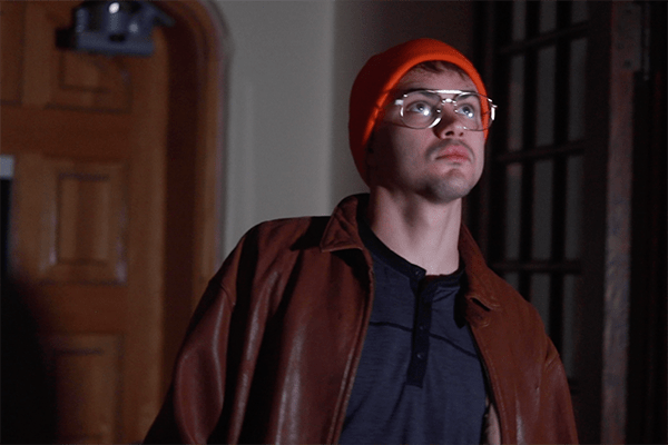 Man in glasses, jacket, and knit hat standing inside a darkened building