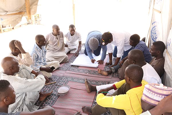 Taking notes during a group discussion after a story circle session with internally displaced persons in Bakassi IDP camp, Maiduguri, Nigeria