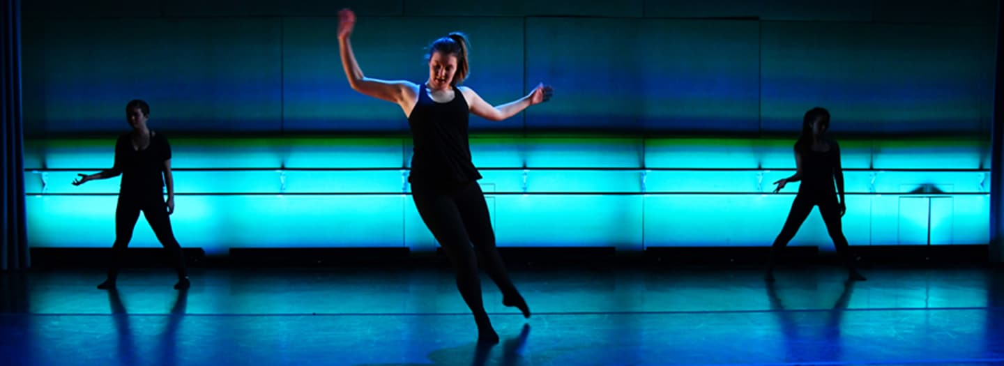 Dancers in black with blue lights on the wall and floor © Thomas Hoebbel Photography~Video