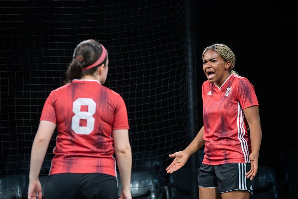 Actors in soccer uniforms on an indoor field. Photo by Rachel Philipson.