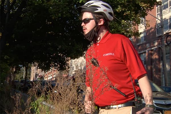 Official in red shirt, sunglasses, and bike helmet on patrol