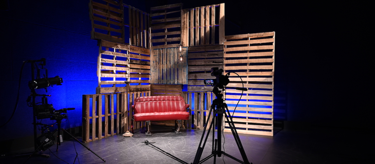 Behind the scenes shot showing cameras pointed at an empty leather backseat from a car set against a dramatically backlit wall made of wooden pallets