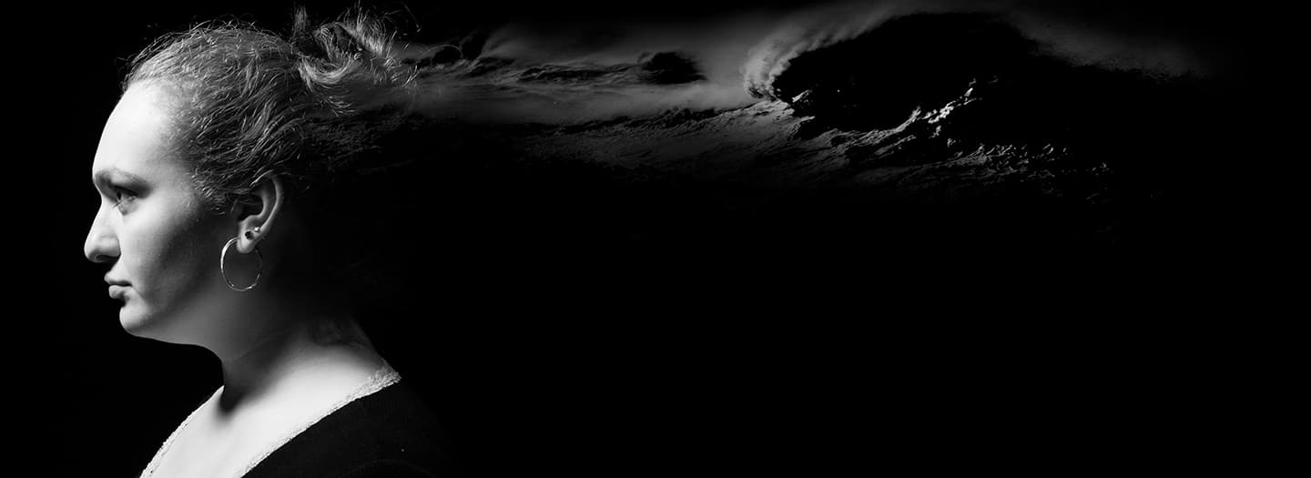 Black and white profile of woman with storm clouds behind her. By Adam Baker.